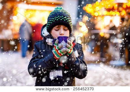 Little Cute Kid Boy Drinking Hot Children Punch Or Chocolate On German Christmas Market. Happy Child