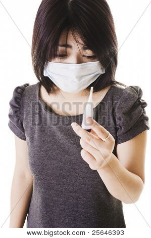 Closeup of a sick Chinese woman wearing a face mask and reading a digital thermometer.