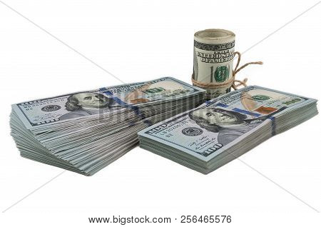 Two Packs Of One Hundred Dollar Bills And A Roll Of Dollars Tied With A Rope On A White Background.