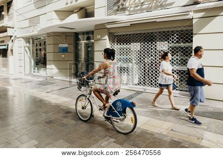 Malaga, Spain - September 2nd, 2018: Woman Riding A Bicycle During A Journey In The City Center Of M