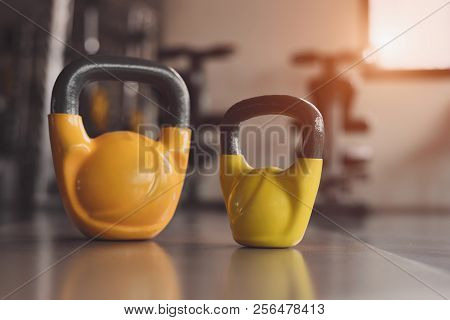 Two Colorful Kettlebells On Fitness Gym Floor. Heavy Weight Sports Equipment And Accessories In Work