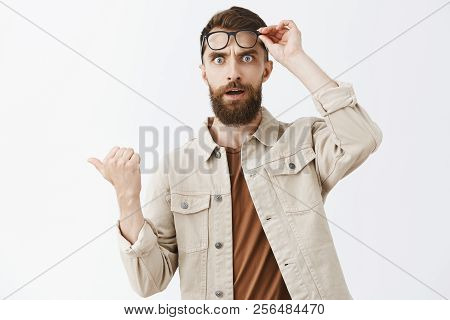 Waist-up Shot Of Concerned Questioned Handsome Mature Male With Beard Taking Off Glasses Staring Sho