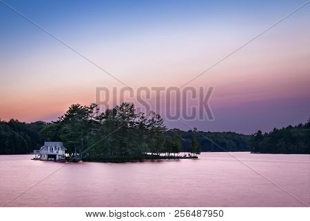 A Small Lakeside Cottage On An Island In The Muskokas, Ontario, At Sunrise.