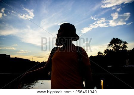 Enjoy pleasant moment. Guy in front of blue sky at evening time admire landscape. Take moment to admire sunset nature beauty. Peace and relax. Man in cap enjoy sunset while stand on bridge poster