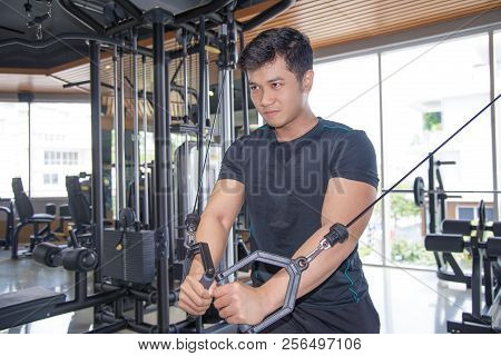 Determined Asian man exercising pecs on gym equipment. Serious guy with gym equipment in background. Bodybuilding concept. poster