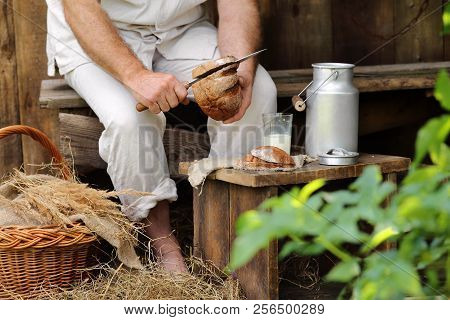 A Man On A Bench In The Garden Cuts Bread
