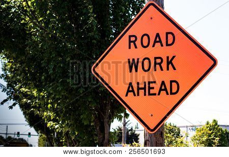 Road Work Ahead Sign On A Post With Trees In The Distance