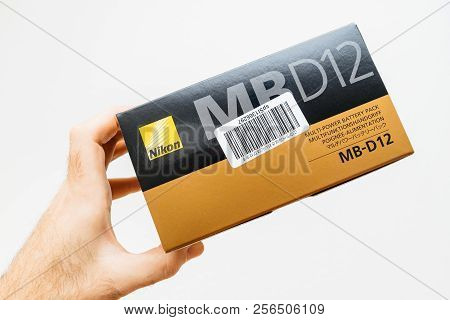 Paris, France - Feb 5, 2018: Photographer Hand Holding Against White Background A Box With Nikon Mb-