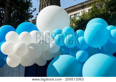 Air balloons background, big bunch of helium balloons, happy birthday, surprise for holiday, decoration. Festive background of blue and white air balloons of different sizes on sky background. poster