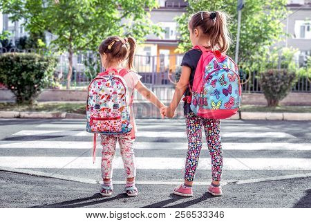 Children Go To School, Happy Students With School Backpacks And Holding Hands Together, Cross The Ro