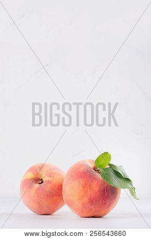 Elegance Ripe Peaches With Green Young Leaves On White Soft Wood Background, Copy Space, Vertical.