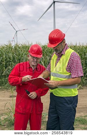 Two Co-workers Wearing Hard Hat Discussing Over Clipboard Document Against Turbines On Wind Farm. Tw
