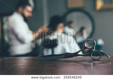 Scissors On A Desk With A Man Getting Trendy Haircut By A Professional Male Hairstylist At The Barbe