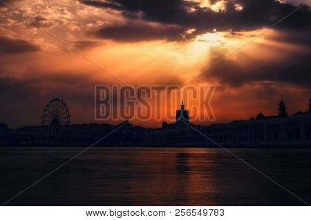 Sun Beams Trough The Clouds In A Cloudy Sunset Through Ferris Wheel And Paseo Del Muelle Uno In Port