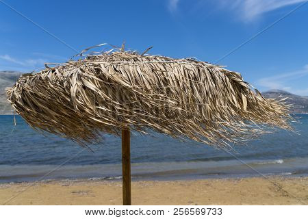 Straw Parasol, Windy Day On The Beach