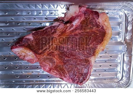 Close-up View Of A Marbled Bone Steak On An Alu Grill Cup
