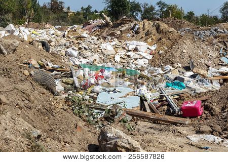 Pollution Of The Environment By People. Illegal Garbage Dump In The Wasteland. A Pile Of Household G