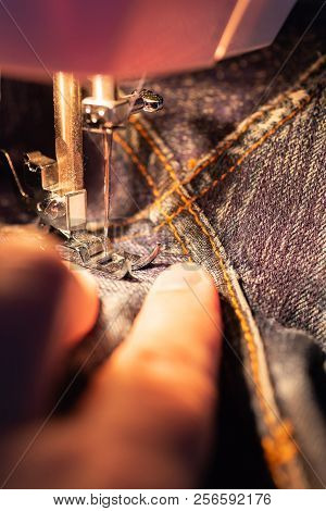 Repair Jeans On The Sewing Machine. View Of The Fabric, Needle And Thread. Illumination From The Bui