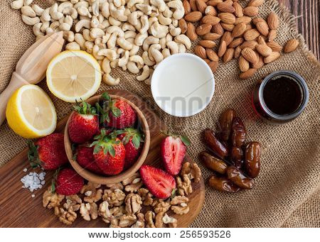 Almonds, Cashews, Walnuts, Dates, Strawberries, Lemon, Coconut Butter, Maple Sirup, Salt On Wooden T