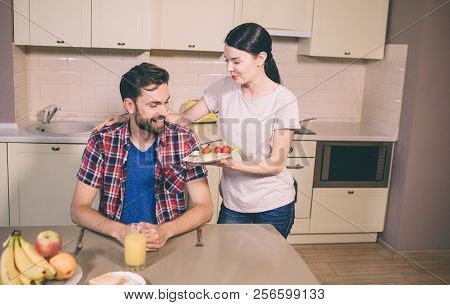 Nice Giel Stands Besides Guy And Give Him Plate With Omlet And Cherry Tomatoes. He Looks At It And S