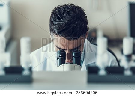 Young Scientist Using Microscope In Laboratory. Male Researcher Wearing White Coat Sitting At Desk A