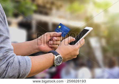 Online Payment, Male Hands Holding A Credit Card And Using Mobile Phone For Online Shopping.