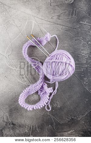 Hanks of woolen lilac threads, knitting needles and a knitting pattern on gray background poster