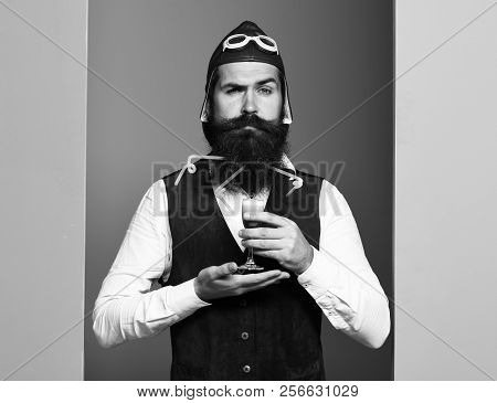 Serious Face Holding Glass Of Alcoholic Shot In Vintage Suede Leather Waistcoat With Hat And Glasses