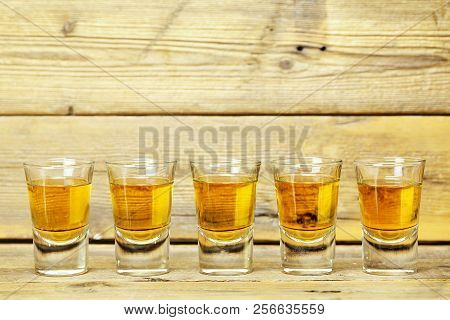 Five Whiskey Shots On Weathered Wooden Planks