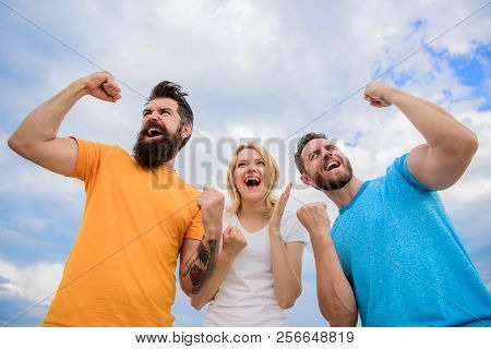 Unbelievable Luck. Threesome Winners Happy With Raised Fists. Woman And Men Look Emotional Successfu