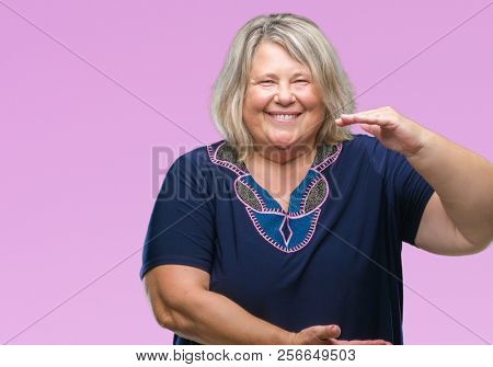 Senior plus size caucasian woman over isolated background gesturing with hands showing big and large size sign, measure symbol. Smiling looking at the camera. Measuring concept.