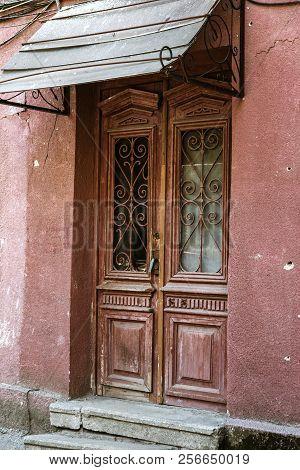 The Old Wooden Door. Ancient Antique Wooden In An Old Wall. Ancient Decorative Wooden Door. Historic