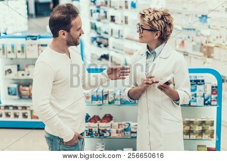 Woman Pharmacist Counseling Customer In Drugstore. Mature Pharmacist Wearing White Coat And Glasses