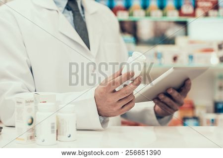 Closeup Pharmacist Holding Pills Bottle And Tablet. Close Up Of Pharmacist Wearing White Coat Holdin