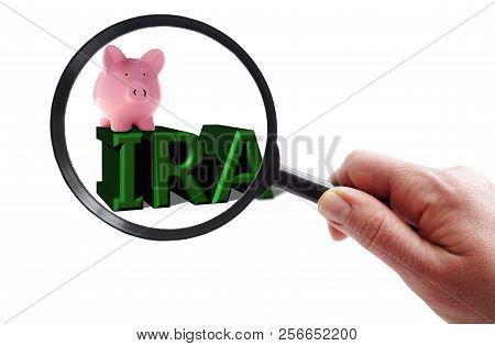 Hand With Magnifying Glass Looking At A Piggy Bank And Ira Text