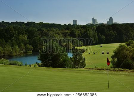 Golfers On An Urban Course In Raleigh, Nc With The City Skyline In The Distance