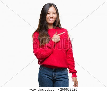 Young asian woman wearing winter sweater over isolated background cheerful with a smile of face pointing with hand and finger up to the side with happy and natural expression on face