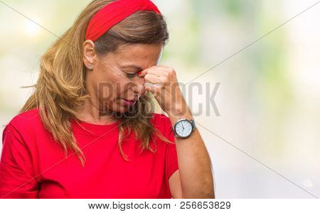 Middle age senior hispanic woman over isolated background tired rubbing nose and eyes feeling fatigue and headache. Stress and frustration concept.