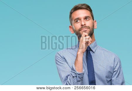 Young handsome business man over isolated background with hand on chin thinking about question, pensive expression. Smiling with thoughtful face. Doubt concept.