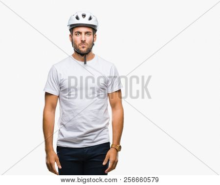 Young handsome man wearing cyclist safety helmet over isolated background with serious expression on face. Simple and natural looking at the camera.