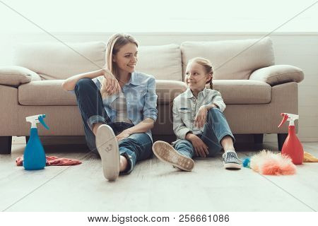 Mother And Daughter Resting After Cleaning House. Young Happy Woman And Smiling Little Girl Resting