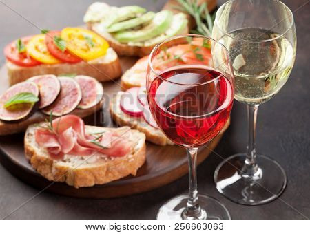 Rose and white wine with brushetta or traditional spanish tapas. Appetizers italian antipasti snacks set on wooden board