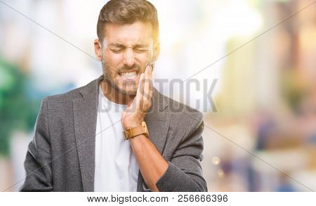 Young handsome business man over isolated background touching mouth with hand with painful expression because of toothache or dental illness on teeth. Dentist concept.