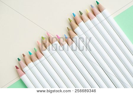 Cute Pale Color Pencils On Pastel Green And Ivory White Paper Background With Copy Space Using As Ad
