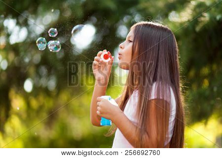 Children girl blowing soap bubbles outdoor