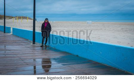 Woman On Boardwalk With Sea Behind Her