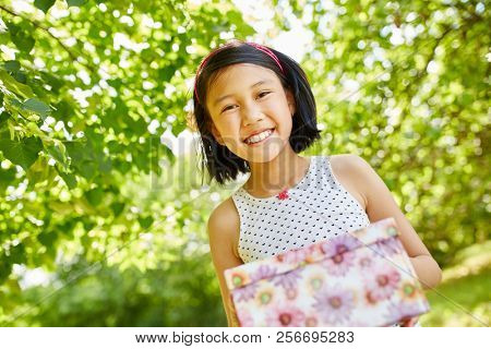 Asian girl as birthday child content with birthday gift