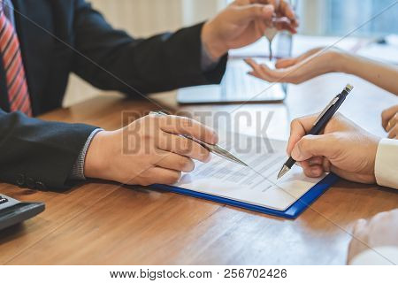 Realtor Giving Keys To A Couple After Successful Deal, A Couple Signing Contract Agreement Document,