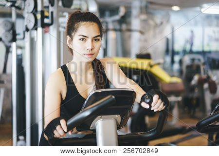 Attractive Woman Riding On The Spinning Bike And Looking At Camera.