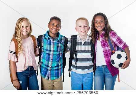Group portrait of pre-adolescent school kids smiling on a white background. Back to school photo of a diverse group of children wearing backpacks